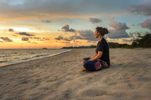 Photograph of a woman mediating on the beach at sunset