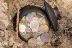 photograph of a pot of coins discovered buried in the ground